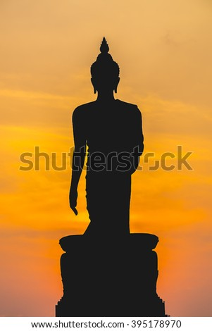 Buddha statue silhouette on red sunset background.