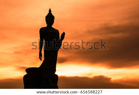 Buddha statue stand on orange sunset, orange sky with the cloud in the background