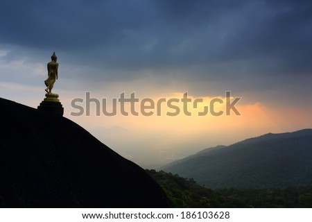 Buddha statue standing on a mountain with beautiful beam, Thailand - stock photo