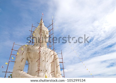 Buddha statue with blue sky and clouds under construction - stock photo