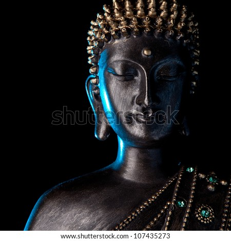 Buddha statue with glow against black background