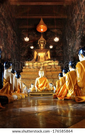 Buddha statues and monk statues sitting in row , Wat Suthat, Thailand, Statue in Buddhist Thailand temple or wat, are public domain or treasure of Buddhism no restrict in copy or use. - stock photo