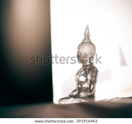 Buddha transparent glass statue close up and blurred