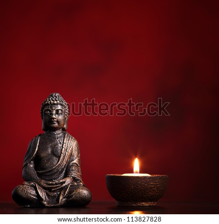 Buddha with burning candle on red background, religious concept. - stock photo