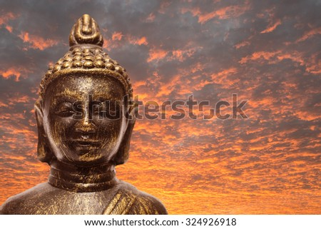 Buddha with orange and red clouds in the sunset