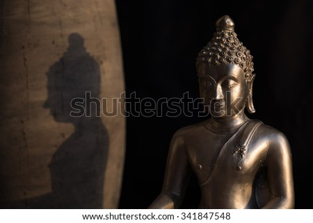 Buddha with shadow in sunlight praying peacefull - stock photo