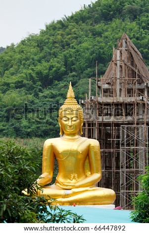 Buddha with the background of under-construction temple on mountain - stock photo