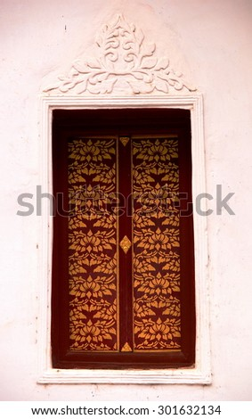 buddhism temple building windows frame in a province in northern THAILAND with decorative colorful golden pattern of ornaments and elements in north THAI style. - stock photo