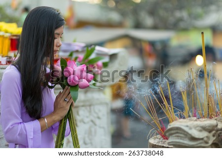 Buddhist Asian woman praying at temple with lotus flower bud bunch - stock photo