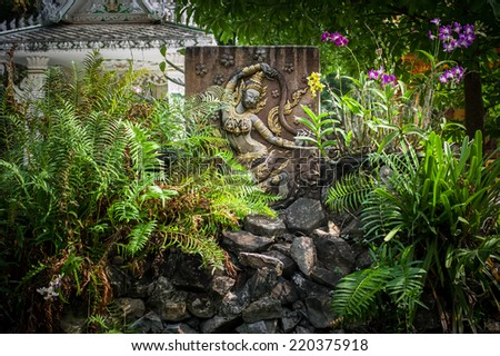 Buddhist carving and pagoda at outdoor park with decorative plants reflecting in pond. Asian city religious architecture at public place. Vientiane, Laos - stock photo