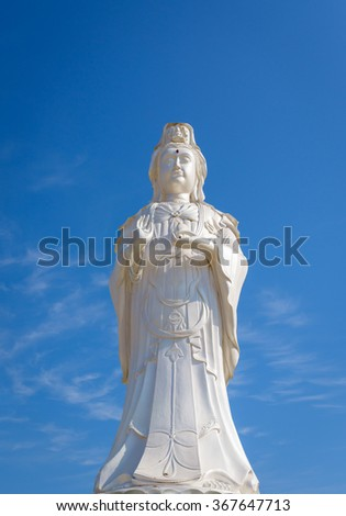 Buddhist figure sculpture, Guanyin Bodhisattva light and shadow on blue sky at thailand