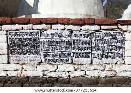 buddhist mani prayer wall on the way to Everest base camp with buddhist tibetan symbols and prayer flags, Khumbu valley, Sagarmatha national park, Nepal - stock photo