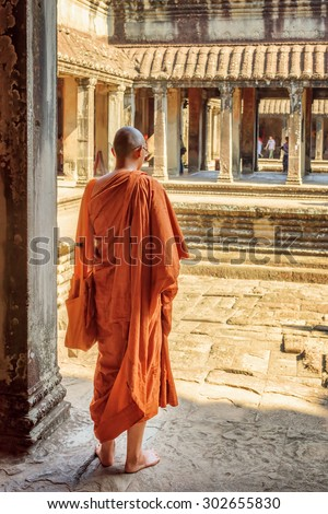 Buddhist monk exploring courtyards of ancient temple complex Angkor Wat in Siem Reap, Cambodia. Mysterious Angkor Wat is a popular destination of tourists and pilgrims. - stock photo