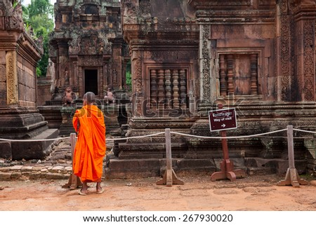 Buddhist monk observing Banteay Srei Temple, one of the temples of legendary Angkor Complex, Seam Reap, Cambodia. - stock photo