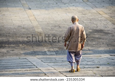Buddhist monk walking down an incline. - stock photo