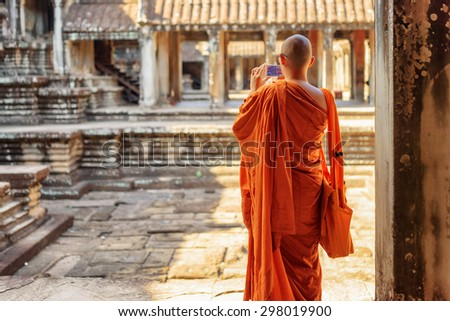 Buddhist monk with smartphone taking picture of courtyard in ancient temple complex Angkor Wat, Siem Reap, Cambodia. Amazing Angkor Wat is a popular destination of tourists and pilgrims. - stock photo