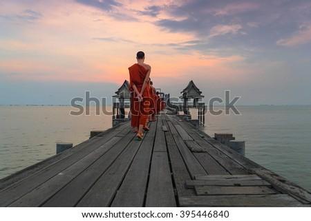 Buddhist monks are walking on a wooden bridge in the evening. Wood bridge. Bridge beautiful twilight sunset. Wood bridge beautiful twilight sunset. - stock photo
