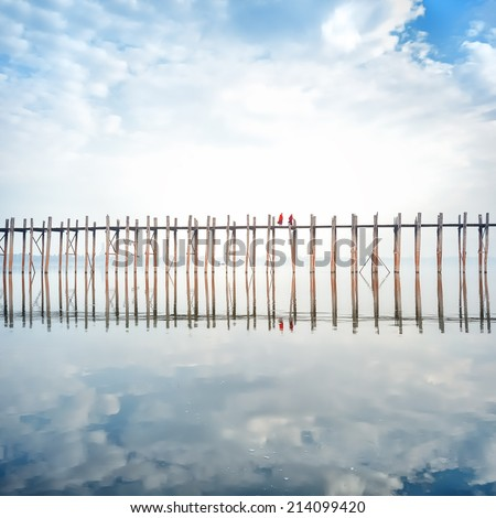 Buddhist monks crossing wooden U Bein bridge in Myanmar - stock photo