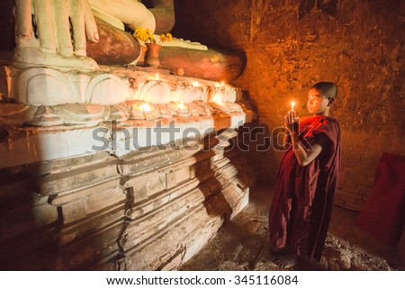 Buddhist novice is praying in temple   - stock photo