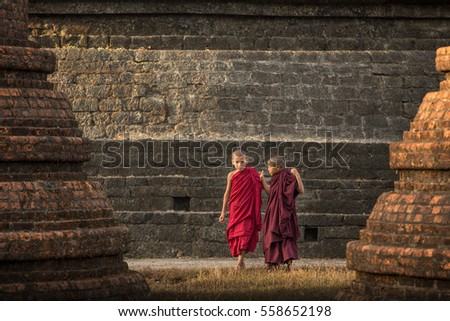 Buddhist novice monks stay outdoors pagoda background, Myanmar.