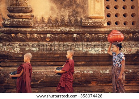 Buddhist novice monks walk to collect alms and offerings at old bagan, Myanmar. This procession is held every morning. - stock photo