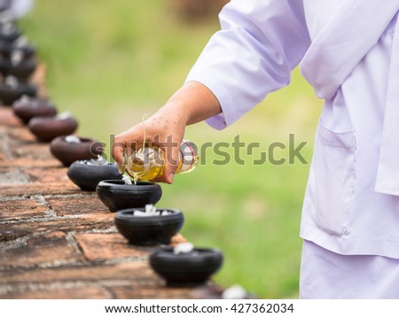 Buddhist pour oil into lamp to prepare candlelit procession in Magha Puja Day - stock photo