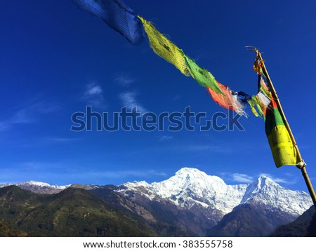 Buddhist prayer flags in the Himalaya mountains, clear blue sky and white mountains, colorful flags, religious flags, mountain traditions, Buddhism traditions, Himalaya mountains traditions, Nepal  - stock photo