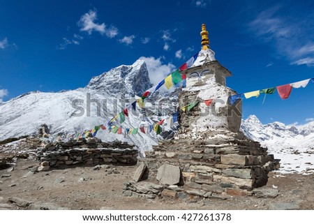 Buddhist prayer flags on a buddhist chorten on Everest Base Camp route in Himalayas, Nepal. Waving buddhist prayer flags in a beautiful mountain landscape near Dingboche village. - stock photo