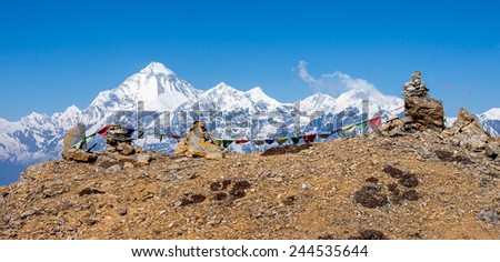 Buddhist prayer flags on cairns in Himalayas with mt. Dhaulagiri in background. - stock photo