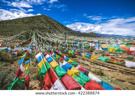 Buddhist prayer flags over the road in Tibet mountains - stock photo