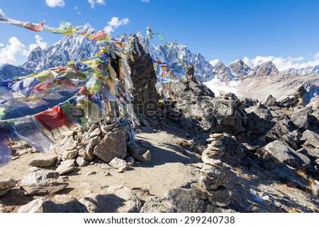 Buddhist prayer flags stones, Gokyo Ri mountain summit peak ascent, snow mountains peaks. Everest Base Camp trail route, trekking Nepal culture, Himalaya ridge traveling. - stock photo