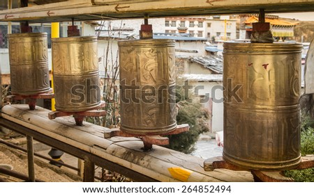 Buddhist prayer wheels in Tibetan monastery with written mantra. - stock photo