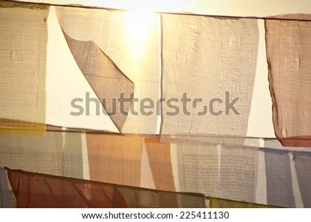 Buddhist praying flags at the sunset  in Lumbini, Nepal - stock photo