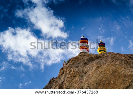 Buddhist religious flags, Blue cloudy sky and mountains of Mulbekh, Himalayan mountains , Ladakh, Jammu and Kashmir, India - stock photo