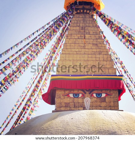 Buddhist shrine Boudhanath Stupa - instagram filter. Stupa with Buddha wisdom eyes and praying flags - retro effect. Colorful praying flags and stupa, Kathmandu, Nepal. - stock photo