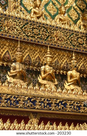 Buddhist statues on the wall of a temple at the Grand Palace in Thailand