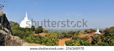 Buddhist stupa and Buddha on a hilltop at Mihintale Monastery, Sri Lanka - stock photo