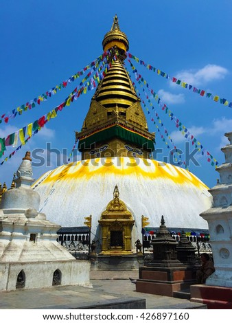Buddhist stupa and flags in Kathmandu, Nepal religious building stupa decorated with flags, buddhist stupa temple in sunny day, nepalese buddhist temple, famous buddhism temple, white and gold temple - stock photo