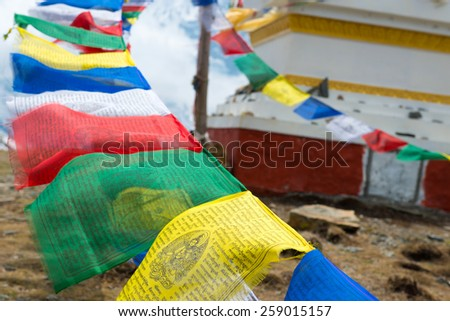 Buddhist stupa with colorful flags on a Annapurna Circuit - most popular tourists trek in Himalayan mountain massive in Nepal.