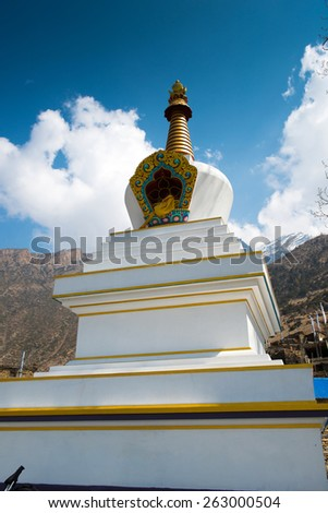 Buddhist stupa with colorful flags on a Annapurna Circuit - most popular turists trek in Himalayan mountain massive in Nepal. - stock photo