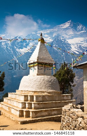 Buddhist stupa with prayer flags in front of the mount Kongde Ri - stock photo