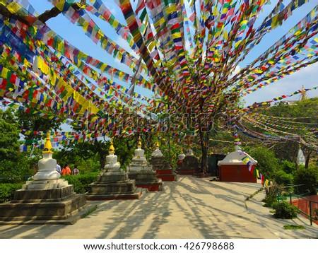 Buddhist stupas and colorful prayer flags, white buddhist stupa line and flag ribbons, white and gold buddhist temple, buddhist temple square, nepalese buddhist stupa, white stupa with eyes, Kathmandu - stock photo