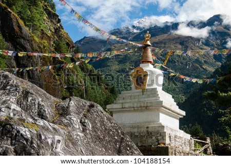 Buddhist stupe or chorten with prayer flags in Himalayas. Religion in Nepal - stock photo