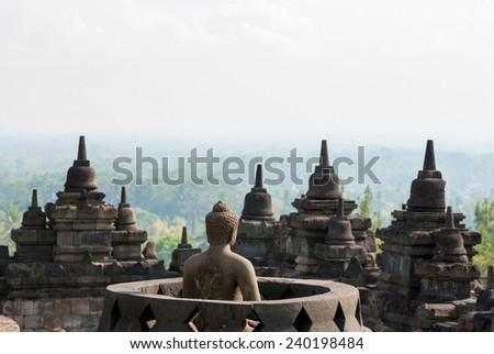 Buddhist temple Borobudor with buddha and stuffa with view over the landscepe arround,  Yogyakarta, Indonesia - stock photo