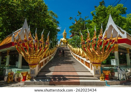 Buddhist temple with stairs and statues against a blue sky - stock photo