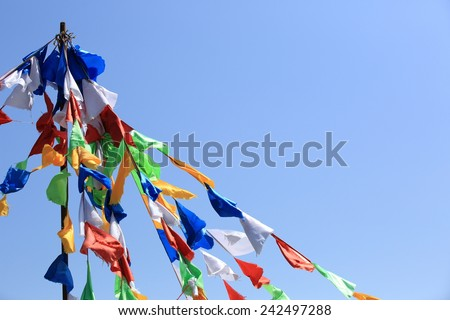 buddhist tibetan prayer flags waving in the wind against blue sky  - stock photo