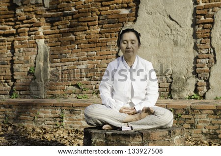 Buddhist woman meditating against ancient temple - stock photo