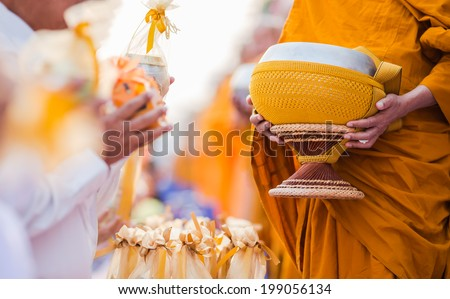 buddhists have faith in buddhism. giving alms to monks - stock photo