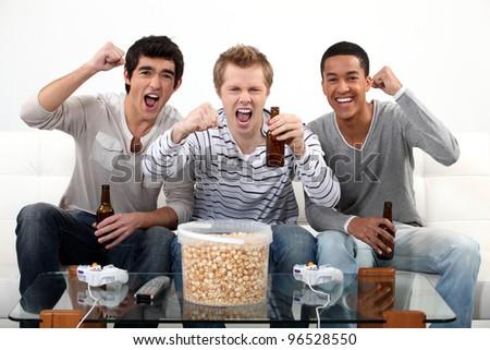 buddies watching football match on telly - stock photo