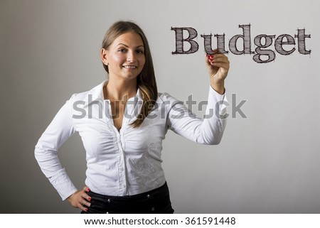 Budget - Beautiful girl writing on transparent surface - horizontal image